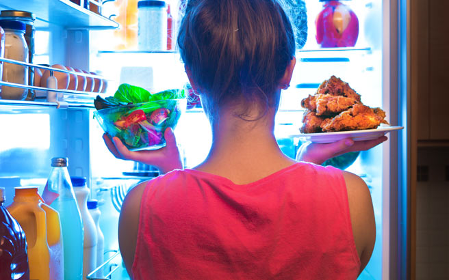 Person standing in front of an open fridge