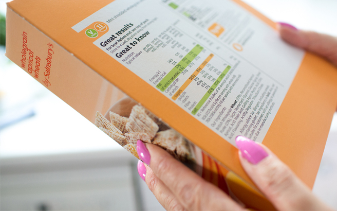 Person examining the nutrition information on a box of food
