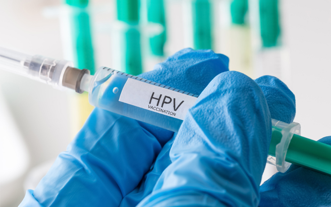 Gloved hand holding syringe labelled HPV vaccination