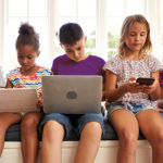 Row of children sat using various electronic devices