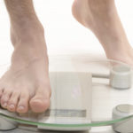 Person stepping onto glass weighing scales
