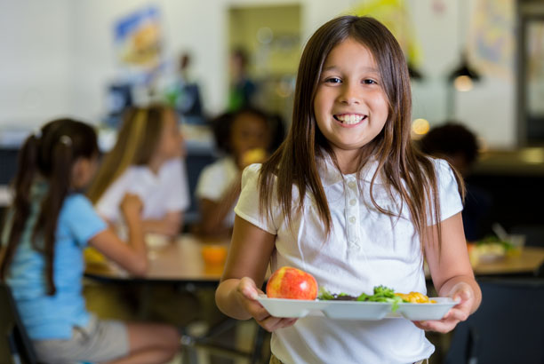 Young school girl with a plate of food