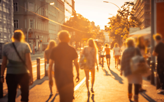 People walking through a sunny city